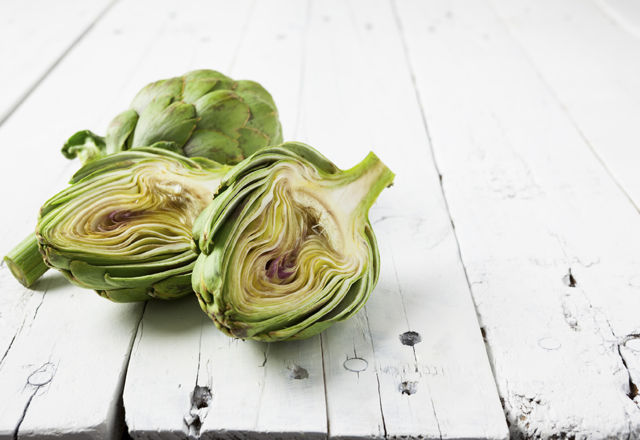 Artichoke cut in half on white with copy space