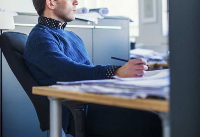 Pensive businessman sitting at desk in office
