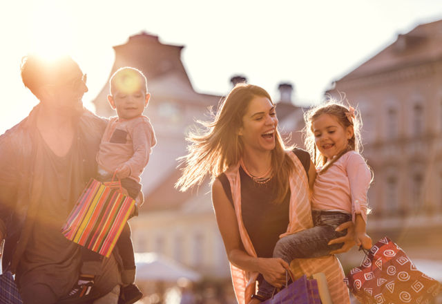 Young cheerful family shopping in the city at sunset.